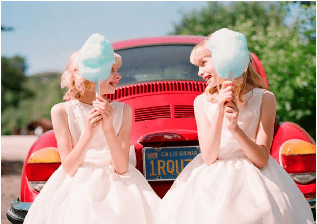 Duas meninas com algodão doce em frente a um carro vermelho