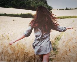 menina corre diante de uma plantação de trigo