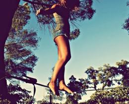 Menina se equilibra em uma corda de slackline, ela mesma é seu próprio guia