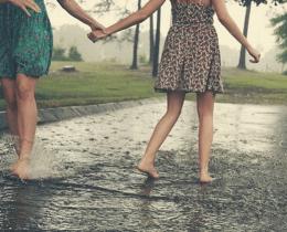 Irmãs de mãos dadas na chuva
