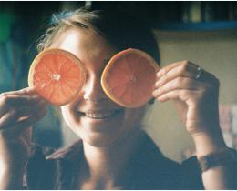Menina com metades da laranja no rosto