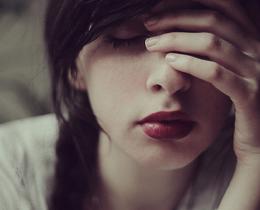 Menina com a mão no rosto, expressão de tristeza e de quem não teve sorte