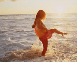 Moça chuta a água do mar