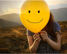 Menina exibe um balão com um sorriso