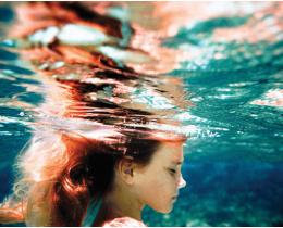 Menina submersa e com os olhos fechados