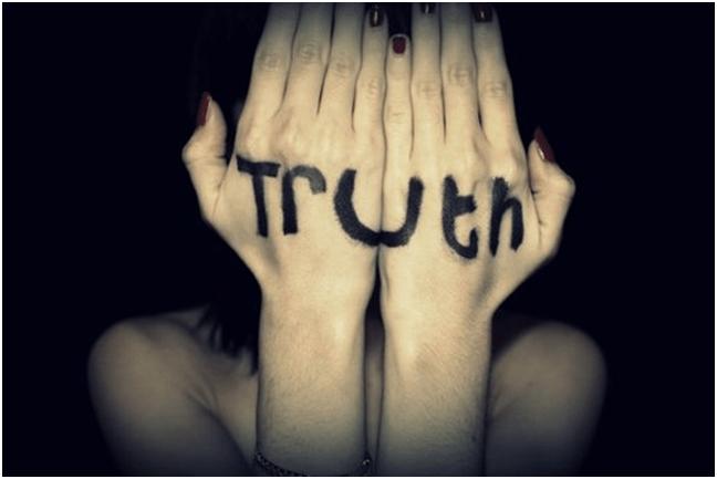 """Mãos com a palavra """"truth"""" esconde o rosto de uma garota"""