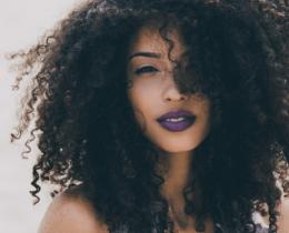Mulher negra, com os cabelos cacheados e naturais
