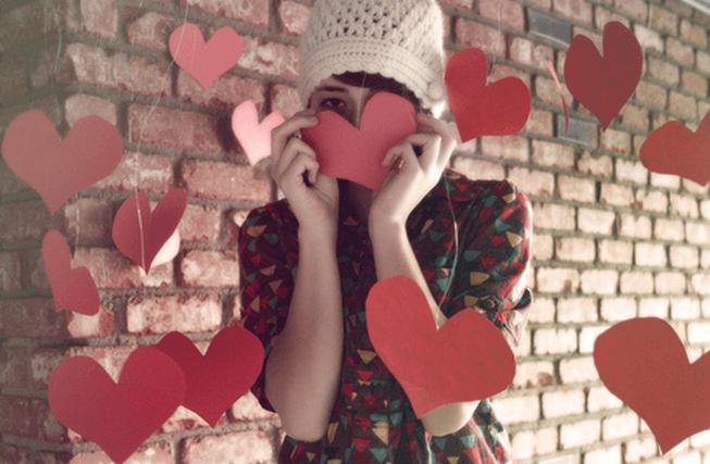 Menina esconde o rosto diante de alguns corações de papel