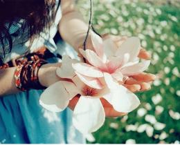 Menina segura uma flor