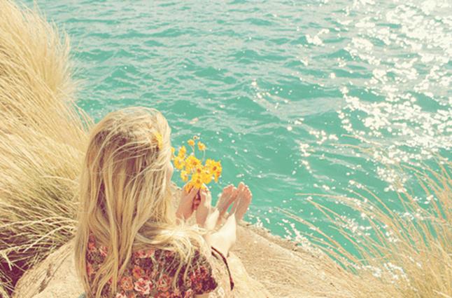 Menina olha o mar com flor na mão, sentada em uma pedra