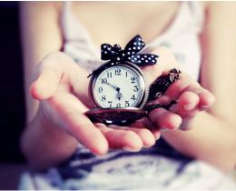 Menina segurando um relógio, simbolizando a perda de tempo para ganhar paz