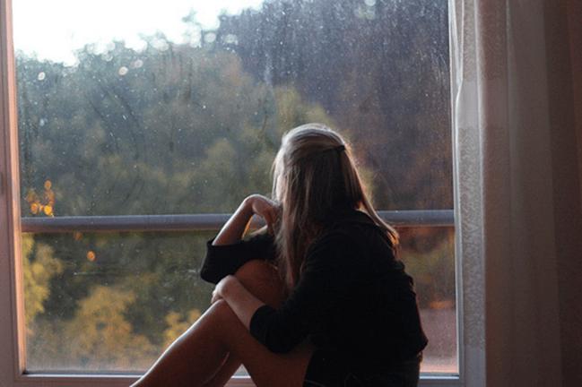 Menina olha para a janela, como quem está procurando demais
