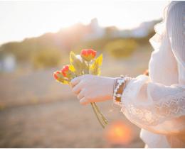 Menina segurando uma flor, ao amar, isso não a torna mais vulnerável