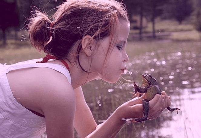 Menina beija sapo, na tentativa de que ele vire príncipe, conforme os contos de fadas.