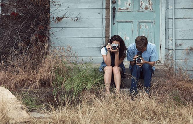 Casal sentado lado a lado com uma máquina de fotografia na mão, sendo bons amigos após um término