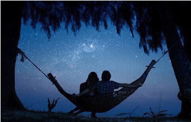 Casal observa os astros, refletindo sobre a astrologia e sua influência