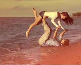 Casal brinca na areia da praia, afirmando a importância do outro para a nossa vida.