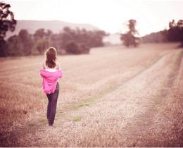 Menina caminha sobre um trilho, refletindo sobre o presente, passado e futuro.