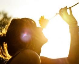 Mulher cheirando uma flor, em homenagem à todas as mulheres